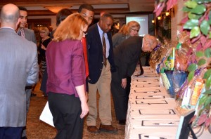 DINING FOR DIVERSITY attendees place their Silent Auction bids for baskets created and donated by Jersey Shore Chapter board members. Honoree Det. Sgt, Cynthia Boyd also donated an item: a platter she designed and made.